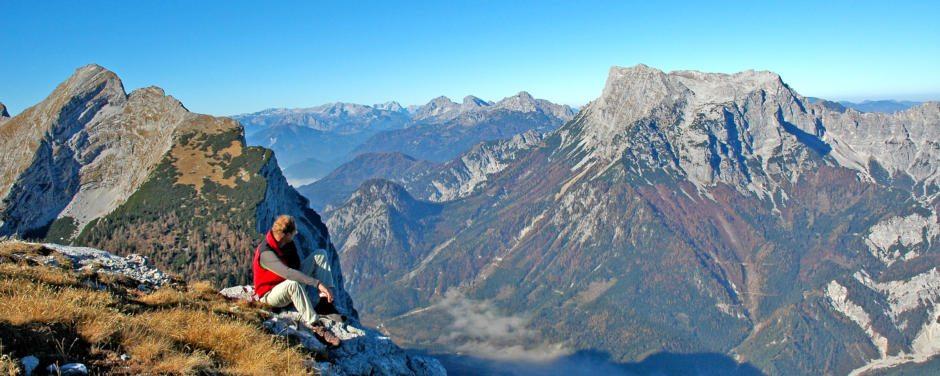 Mann macht eine Wandernpause und genießt herrlichen Ausblick im Nationalpark Gesäuse in der Steiermark. JUFA Hotels bieten erholsamen Familienurlaub und einen unvergesslichen Winter- und Wanderurlaub.