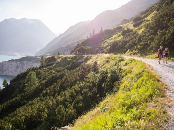 Sie sehen einen Wanderweg mit Wanderern an einem See mit Bergen. JUFA Hotels bietet Ihnen den Ort für erlebnisreichen Natururlaub für die ganze Familie.