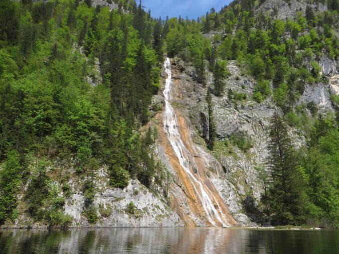 Sie sehen einen Wasserfall am Toplitzsee im Sommer. JUFA Hotels bietet tollen Sommerurlaub an schönen Seen für die ganze Familie.