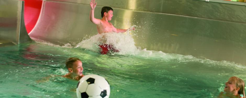 Sie sehen wie Kinder auf der Wasserrutsche im Hallenbad des JUFA Hotel Veitsch rutschen. Der Ort für kinderfreundlichen und erlebnisreichen Urlaub für die ganze Familie.