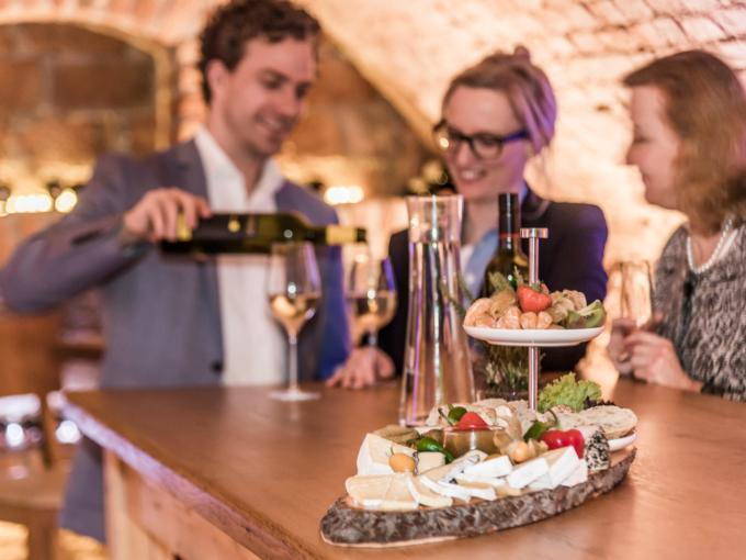 Sie sehen den Weinkeller im JUFA Hotel Wien City mit einer Jause. JUFA Hotels bietet erlebnisreichen Städtetrip für die ganze Familie und den idealen Platz für Ihr Seminar.