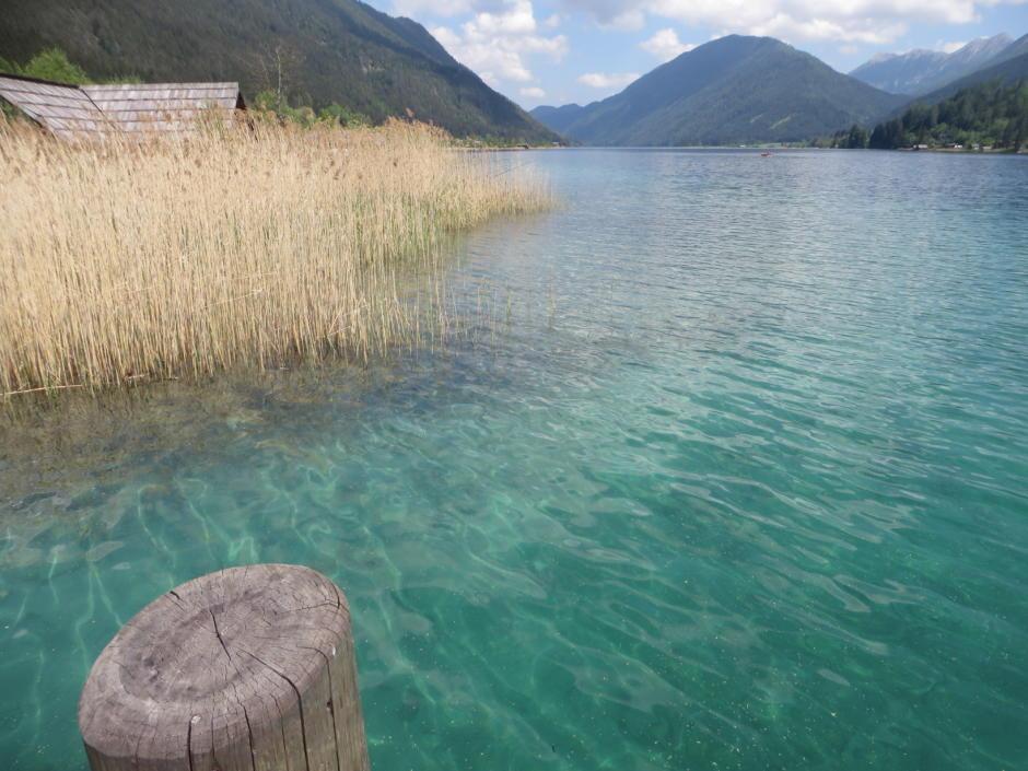 Sie sehen den Weissensee in Kärnten mit seinen umliegenden Bergen. JUFA Hotels bietet tollen Sommerurlaub an schönen Seen für die ganze Familie.