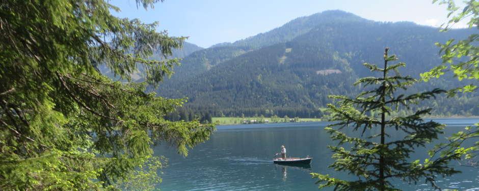 Sie sehen den Weissensee in Kärnten mit einem Boot. JUFA Hotels bietet tollen Sommerurlaub an schönen Seen für die ganze Familie.