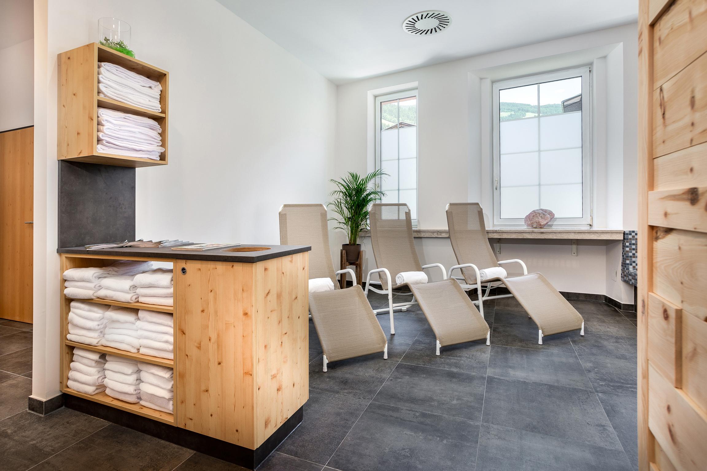 Sie sehen den Wellnessbereich mit Liegestühlen und Handtüchern im JUFA Alpenhotel Saalbach. Der Ort für erholsamen Familienurlaub und einen unvergesslichen Winter- und Wanderurlaub.