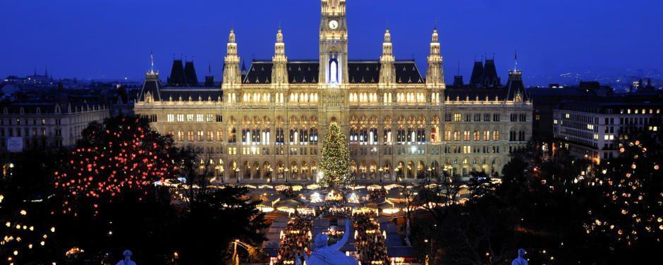 Aussenansicht des beleuchteten Wiener Rathauses bei Nacht mit Weihnachtsmarkt im Winter. JUFA Hotels bietet erlebnisreichen Städtetrip für die ganze Familie und den idealen Platz für Ihr Seminar.