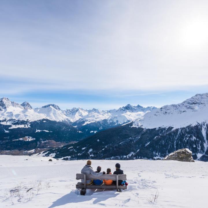 Sie sehen eine Familie beim Entspannen auf einer Bank. JUFA Hotels bietet erholsamen Familienurlaub und einen unvergesslichen Winterurlaub.