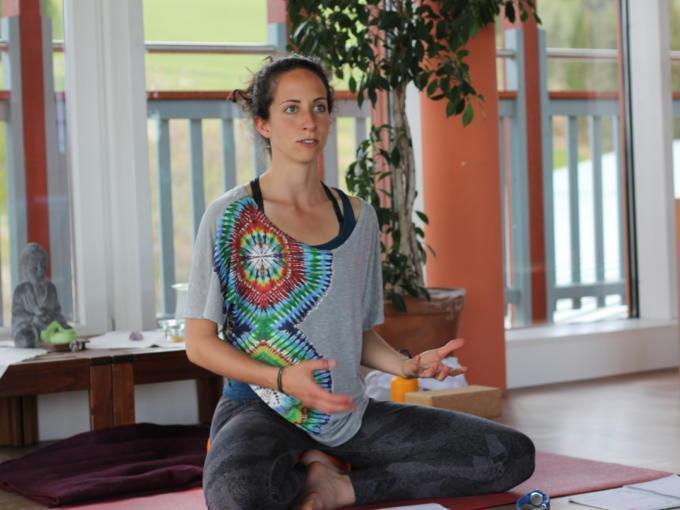 Sie sehen eine Yoga-Lehrerin im JUFA Hotel Knappenberg auf einer Yoga-Matte. JUFA Hotels bietet erholsamen Familienurlaub und einen unvergesslichen Winter- und Wanderurlaub.
