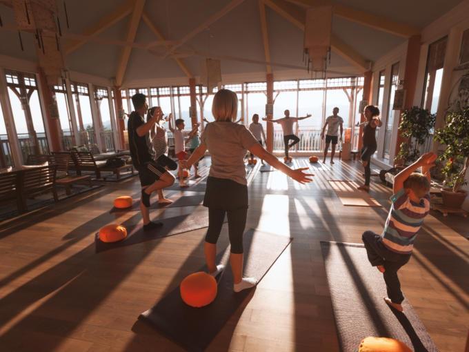 Eine Yogagruppe macht Yoga im Sonnengrußraum und durch die tiefstehende Sonnen werfen die Teilnehmer lange Schatten.JUFA Hotels, der Ort für erholsamen Familienurlaub und einen unvergesslichen Winter- und Wanderurlaub.