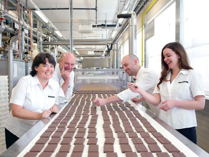 Sie sehen die Familie Zotter am Produktionslaufband der Zotter Schokoladen Manufaktur. JUFA Hotels bieten erholsamen Familienurlaub und einen unvergesslichen Winter- und Wanderurlaub.